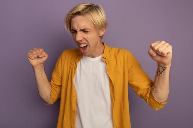 Взволнованный, с закрытыми глазами молодой блондин в желтой футболке показывает жест да, изолированный на фиолетовом