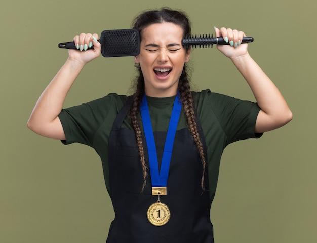 目を閉じて興奮している若い女性の理髪師は、オリーブグリーンの壁に隔離された寺院の制服とメダル保持櫛で