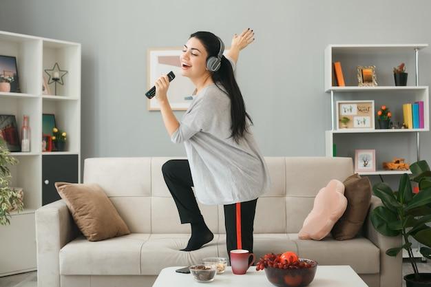 Eccitato con gli occhi chiusi, giovane ragazza che indossa le cuffie che tiene il telecomando della tv canta in piedi sul divano dietro il tavolino da caffè nel soggiorno