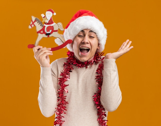 Excited with closed eyes young guy wearing christmas hat with garland on neck holding christmas toy spreading hand isolated on yellow wall