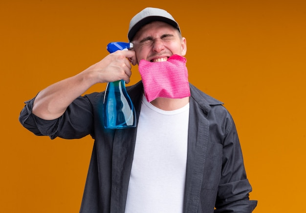 Excited with closed eyes young handsome cleaning guy wearing t-shirt and cap holding rag in mouth putting spray bottle on temple isolated on orange wall
