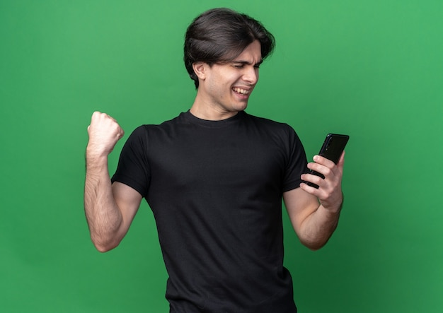 Excited with closed eyes young handsome guy wearing black t-shirt holding phone showing yes gesture isolated on green wall