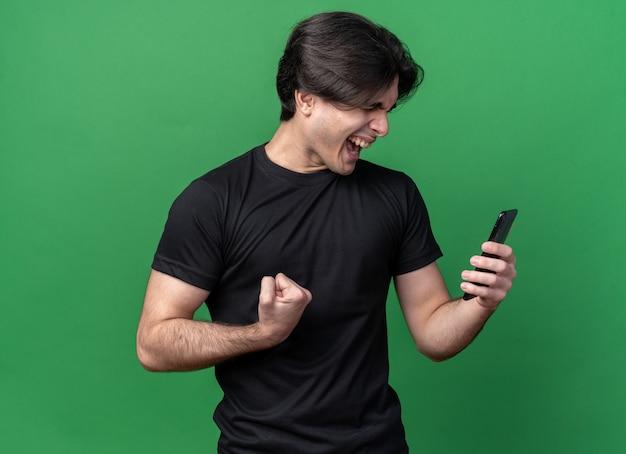 닫힌 된 눈으로 흥분 젊은 잘 생긴 남자 녹색 벽에 고립 예 제스처를 보여주는 전화를 들고 검은 티셔츠를 입고