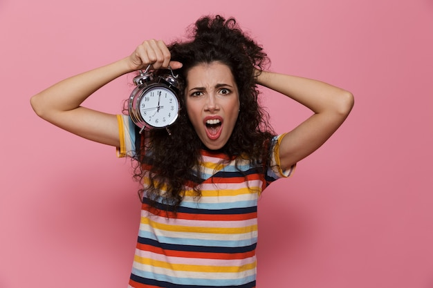 ピンクで隔離の目覚まし時計を保持している巻き毛の興奮した女性20代