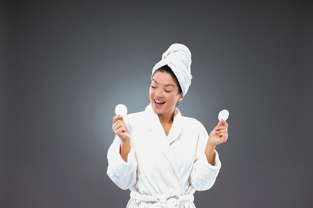 Excited woman in a bathrobe and a towel wrapped around her head holds a cotton white pad while standing in front of a gray wall