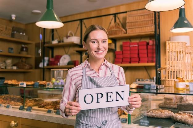 흥분된 여자. 자신의 프랑스 빵집을 여는 흥분된 아름다운 녹색 눈의 사업가