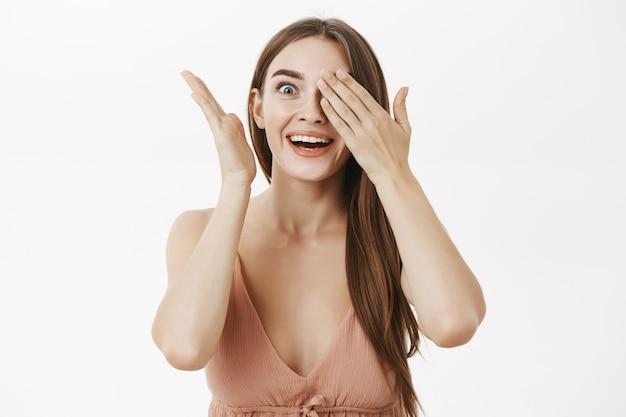 興奮した女性は驚きで片手で覗く手のひらで目を覆っている内部に驚きを保持することはできません
