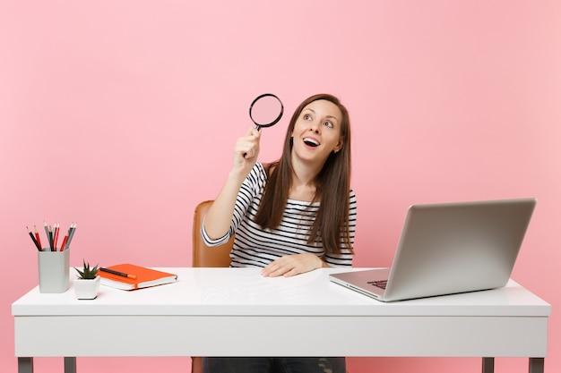 Excited woman in casual clothes looking up through magnifying glass work at white desk with contemporary pc laptop