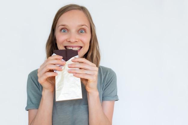 Взволнованная женщина ест шоколад в золотой фольге