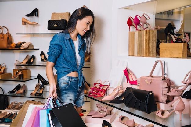 Возбужденная женщина, исследующая полки в магазине