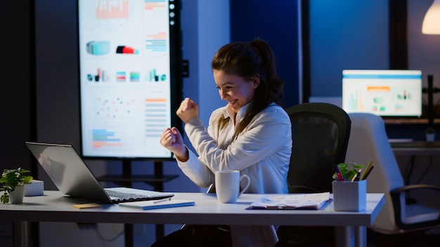 Возбужденная женщина чувствует себя в восторге, читая отличные онлайн-новости о ноутбуке, работающем сверхурочно в офисе начинающей компании. счастливый сотрудник, использующий современные технологии беспроводной сети, учится писать, искать