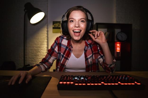 Взволнованная женщина-геймер сидит за столом, играет в онлайн-игры на компьютере в помещении, празднует успех