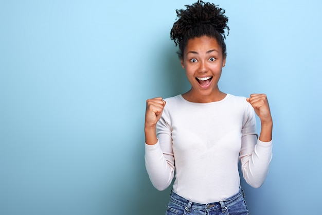 Excited woman hands up with clenched fists in winner gesture