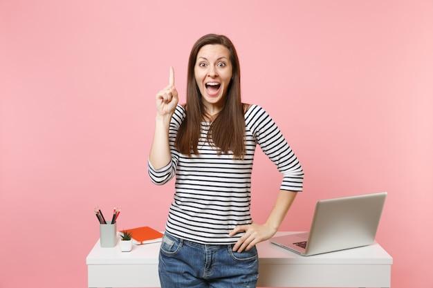 パステルピンクの背景に分離されたラップトップで机の近くに立って人差し指を考えて新しいアイデアを持っている興奮した女性。業績ビジネスキャリアコンセプト。広告用のスペースをコピーします。