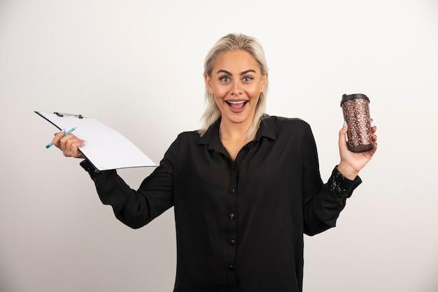 흰색 바탕에 클립 보드와 컵을 들고 흥분된 여자. 고품질 사진