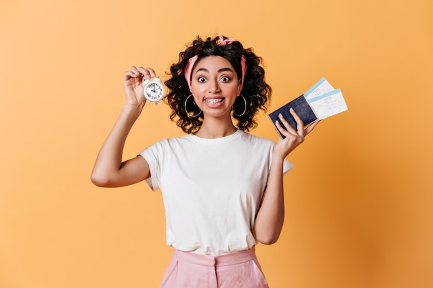 Excited woman holding alarm clock on yellow wall