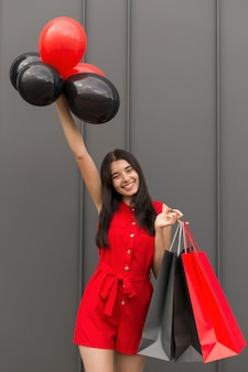 Excited woman holding balloons and shopping bags front view