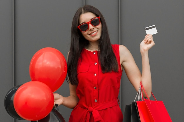Excited woman holding balloons and shopping card medium shot