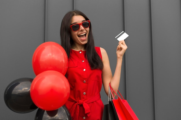 Excited woman holding balloons and shopping card