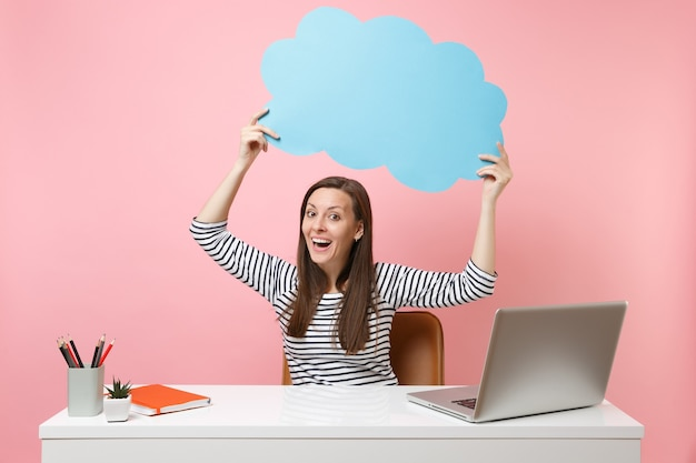 Excited woman holding blue empty blank say cloud speech bubble work at white desk with pc laptop isolated on pastel pink background. achievement business career concept. copy space for advertisement.