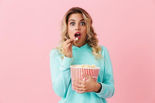 Возбужденная женщина держит ведро с попкорном и смотрит в камеру, изолированную над розовой стеной