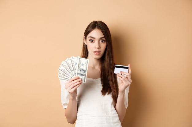 ドル札とプラスチックのクレジットカードを持っている興奮した女性は、beigに立っているカメラに驚いています...