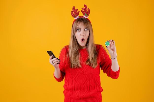 Взволнованная женщина держит зеленый покер чип из онлайн-казино и показывает телефон с пустым экраном