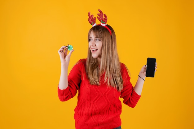 Excited woman holding green poker chip from online casino and showing phone with blank screen