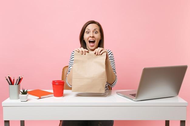 Возбужденная женщина, держащая в руке коричневый прозрачный пустой пустой бумажный мешок ремесла, работает в офисе с ноутбуком, изолированным на розовом фоне. доставка продуктов курьерской службой из магазина или ресторана в офис.