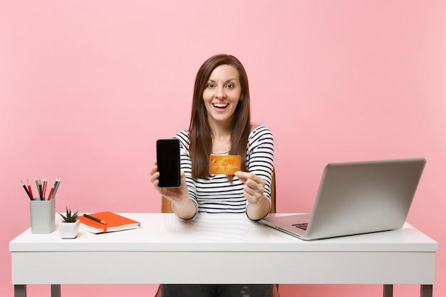 Возбужденная женщина, держащая мобильный телефон с пустым пустым экраном, кредитная карта сидит за белым столом с современным ноутбуком, изолированным на пастельно-розовом фоне. достижение деловой карьеры. скопируйте пространство.