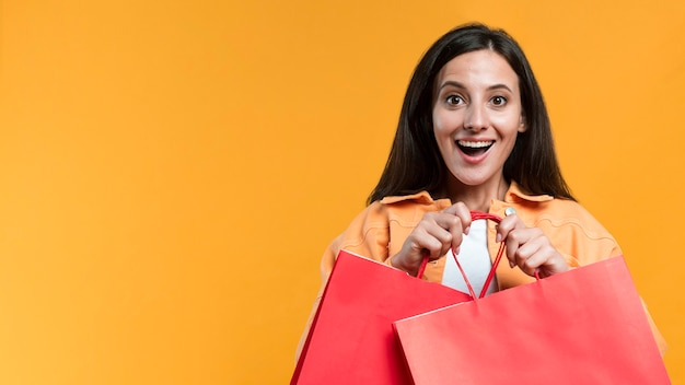 Excited woman holding shopping bags with copy space