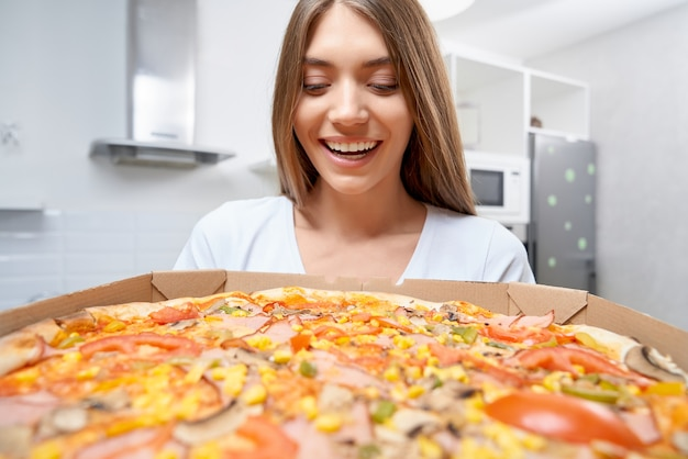 Excited woman holding tasty pizza