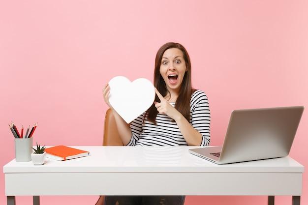パステルピンクの背景に分離されたpcラップトップでオフィスに座っている間プロジェクトに取り組んでいるコピースペースで白いハートを保持している興奮した女性。業績ビジネスキャリアコンセプト。広告エリア。