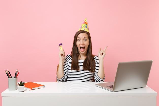 생일 파티 모자를 쓴 흥분한 여성, pc 노트북으로 책상에 앉아 일하는 동안 축하하는 파이프 연주