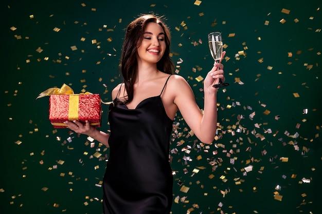 검은 드레스를 입은 흥분한 여성이 빨간색 선물 상자와 샴페인 파티 시간 휴가 컨셉의 유리를 들고 있습니다