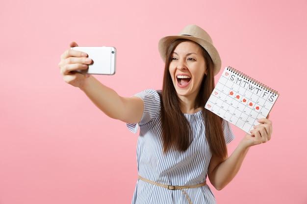 ピンクの背景で隔離の月経日をチェックするための期間カレンダーを保持し、携帯電話で自分撮りをしている青いドレスの興奮した女性。医療、ヘルスケア、婦人科の概念。スペースをコピーします。