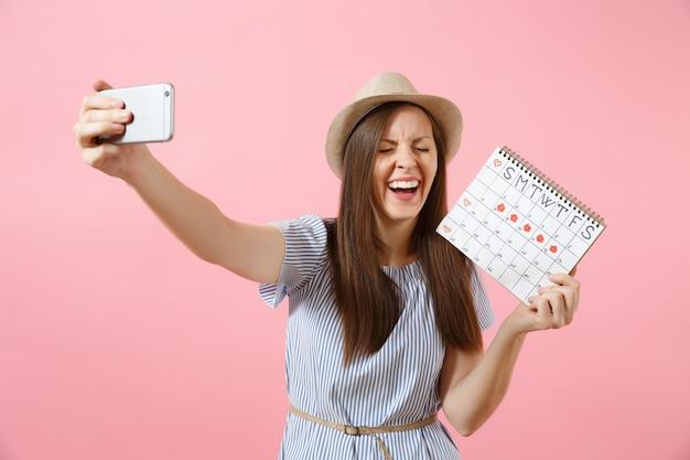 Возбужденная женщина в синем платье делает селфи на мобильном телефоне, держа календарь периодов для проверки дней менструации, изолированных на розовом фоне. медицина, здравоохранение, гинекологическая концепция. скопируйте пространство.