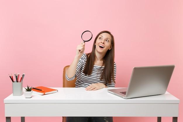 파스텔 핑크 배경에 격리된 현대적인 pc 노트북이 있는 흰색 책상에서 돋보기를 통해 올려다보는 캐주얼 옷을 입은 흥분한 여성. 성취 비즈니스 경력 개념입니다. 공간을 복사합니다.