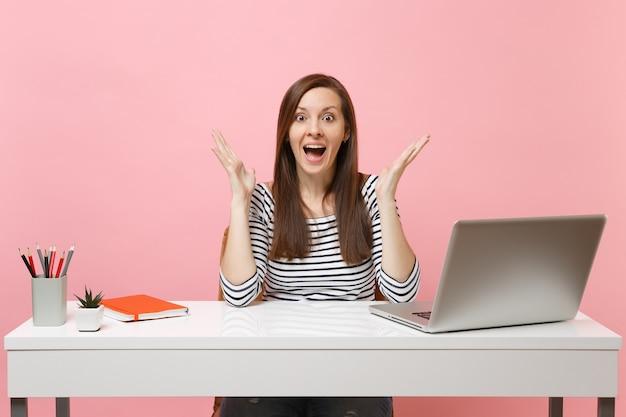 평상복 차림의 흥분한 여성이 손을 벌리고, 현대적인 pc 노트북이 있는 흰색 책상에 앉아