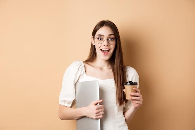 테이크 아웃 컵에서 커피를 마시고, 노트북을 들고, 베이지 색에 서 행복 하 게 웃 고 안경에 흥분된 여자.