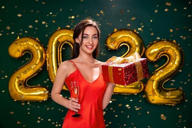 빨간 드레스를 입은 흥분한 여성이 선물 빨간 상자와 샴페인 파티 시간 휴가 컨셉의 유리를 들고 있습니다