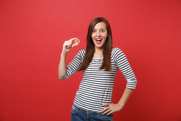 흥분한 여성이 입을 크게 벌리고 놀란 표정을 하고 빨간색 배경에 격리된 금색 미래 통화의 비트코인 금속 동전을 들고 있습니다. 사람들은 진실한 감정, 라이프 스타일. 복사 공간을 비웃습니다.