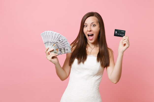 Excited woman in lace white dress holding bundle lots of dollars, cash money and credit card