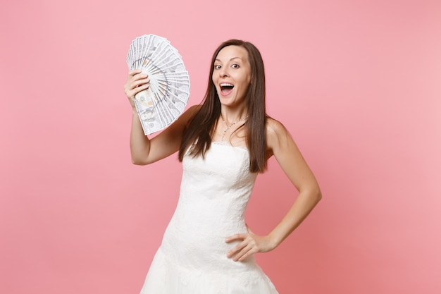 Excited woman in lace white dress holding bundle lots of dollars cash money