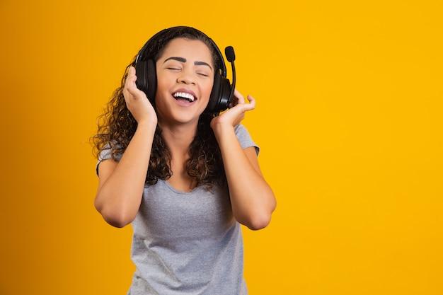 ヘッドフォンで音楽を聴いている興奮した女性。