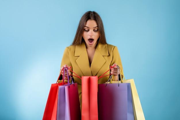 파란색 통해 격리 된 다채로운 쇼핑 가방을 찾고 흥분된 여자