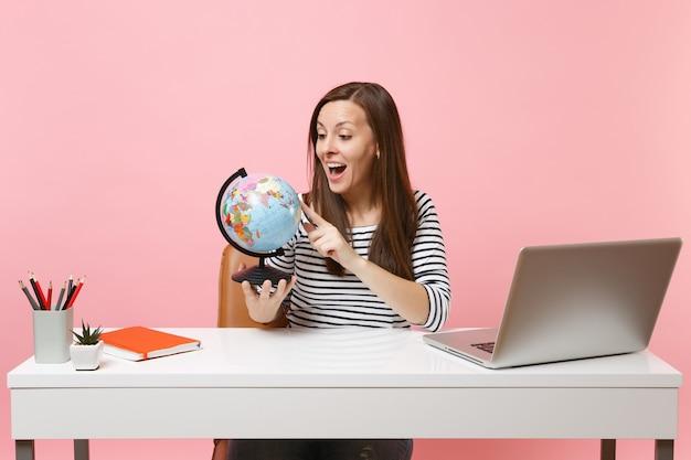 パステルピンクの背景に分離された現代的なpcのラップトップで白い机に座って仕事をしながら世界の地球儀計画休暇を探している興奮した女性。業績ビジネスキャリアコンセプト。スペースをコピーします。