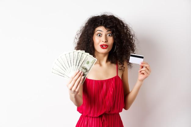 驚きと不信感を持って見て興奮した女性は、白い背景の上の赤いドレスに立って、ドルの賞品とプラスチックのクレジットカードを示しています。