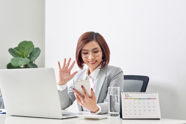 興奮した女性は、ラップトップで机に座って仕事をしながら携帯電話で自分撮りショットを撮って挨拶するために手を振ってビデオ通話をします