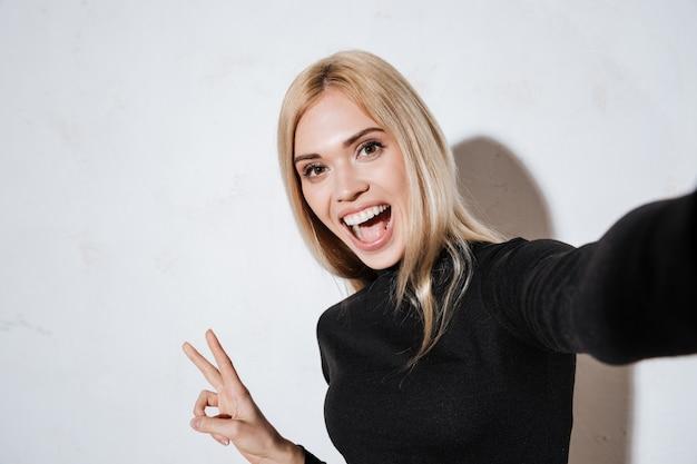 Donna emozionante che fa selfie e che mostra gesto di pace in studio